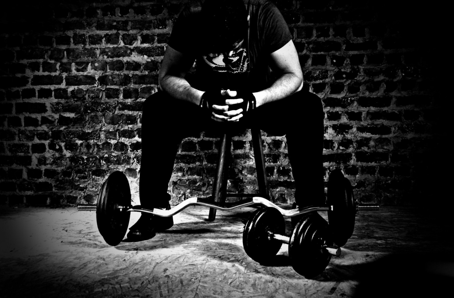 black and white of man on stool leaning over barbell and weights