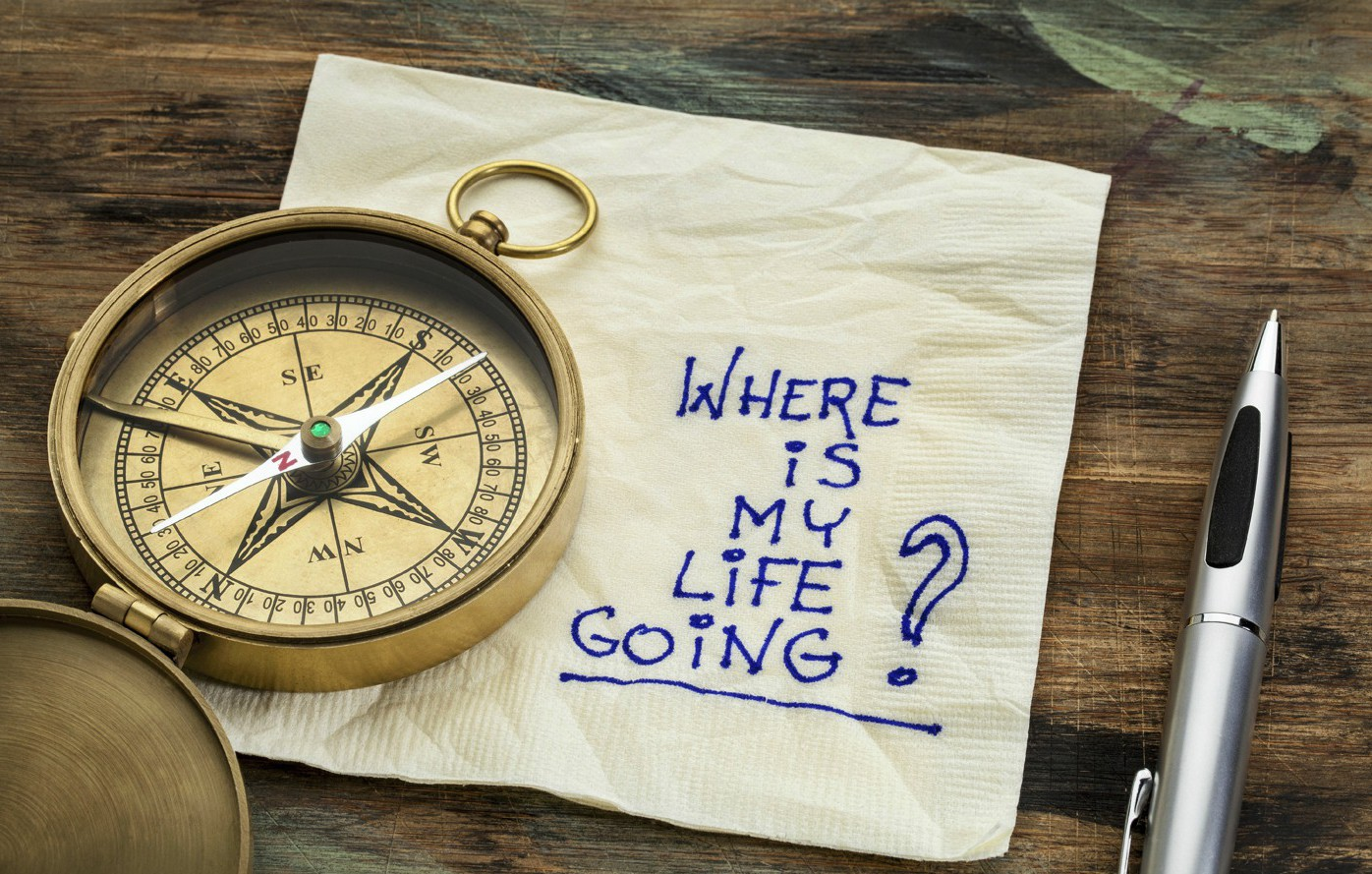 Compass laying on napkin with the words Where is my life going? wirtten on the napkin