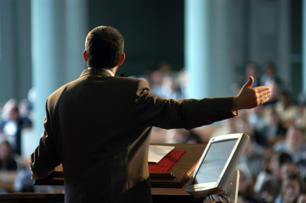 Preacher at pulpit preaching, photo taken from behind