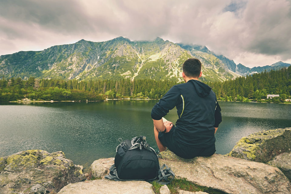 Contented man on cliff looking over water with mountain in the distance