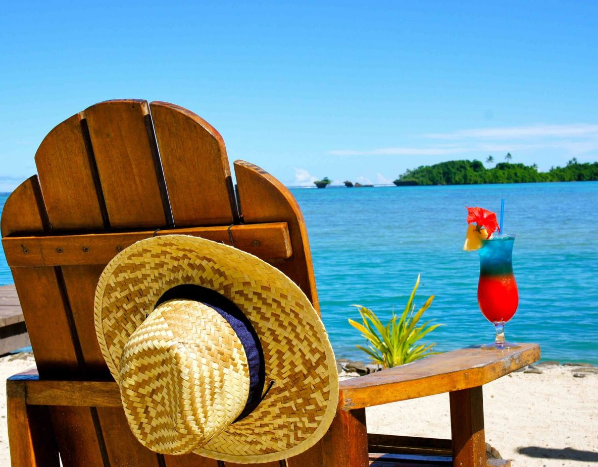 Beach chair with hat and drink on beach
