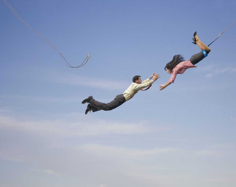 trapeze business man and woman - man with outstretched arms in midair